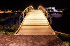 Illuminated heavenly bridge going over lake. Portrait shot of a golden bridge Stock Photography