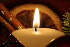 Illuminated holiday candle. With orange peel, cinnamon sticks and pine bough Stock Photography