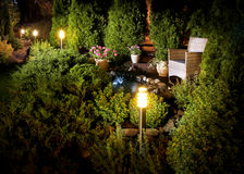 Illuminated home garden fountain patio. Illuminated home garden patio, plants and evening lights near small fountain Royalty Free Stock Photo