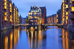 Illuminated house and two brides in Speicherstadt, Hamburg Stock Photo