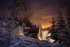 Illuminated house in winter forest Stock Photo