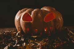 Illuminated jack o lantern with leaves on table during autumn. Close up of illuminated jack o lantern with leaves on table during autumn Royalty Free Stock Images