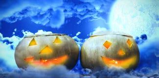 Composite image of illuminated jack o lanterns on table. Illuminated jack o lanterns on table against moon shining between clouds Royalty Free Stock Photos
