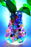 Illuminated jar with colourful balls & water plant Stock Image
