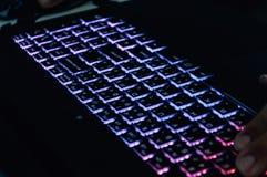 Illuminated keyboard gaming in low light stock photo