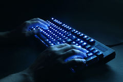 Illuminated keyboard. male hands typing on a computer. Royalty Free Stock Photos