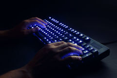 Illuminated keyboard. male hands typing on a computer. Stock Photo