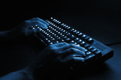 Illuminated keyboard. male hands typing on a computer. Royalty Free Stock Image