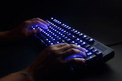 Illuminated keyboard. male hands typing on a computer. Stock Photography