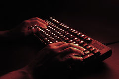 Illuminated keyboard. male hands typing on a computer. Hacker or programmer at work. on a black background. red tint royalty free stock photo
