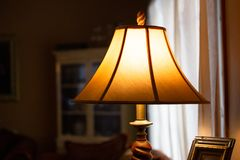 Illuminated lamp with shade in a dimly lit room. Image of Illuminated lamp with shade in a dimly lit room stock photos