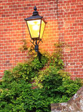 Illuminated lantern against brick wall Royalty Free Stock Photo