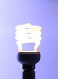 Illuminated light bulb. Illuminated compact light bulb on a purple background symbolising a bright idea Royalty Free Stock Photo