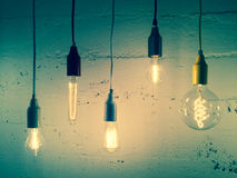 Illuminated light bulbs on green background Royalty Free Stock Image