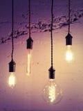Illuminated light bulbs on purple background Royalty Free Stock Photos