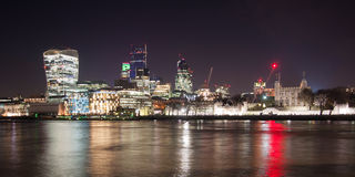 Illuminated London skyline by night. London skyline by the Thames river at night Royalty Free Stock Photo