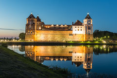 Illuminated medieval castle in the Belorussian town of Mir at night with reflection in a pond on sunset background Royalty Free Stock Images