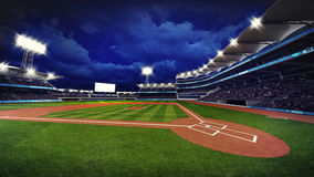 Illuminated modern baseball stadium with spectators and green grass Royalty Free Stock Image