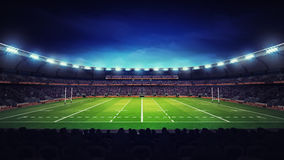 Illuminated modern rugby stadium with spectators and green grass Royalty Free Stock Images