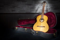 Illuminated music guitar with case in fron. Illuminated classic music guitar with case in front of leather and stone wall Stock Image