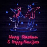 Illuminated neon signs winter holiday light electric banner glowing on black brickwall. Happy new year and merry Christmas 2019 text concept with ice skating stock illustration