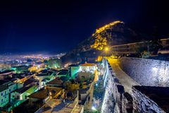 Illuminated old town of Nafplion in Greece. Illuminated old town of Nafplion in Greece with tiled roofs, small port, bourtzi castle, Palamidi fortress at night stock image