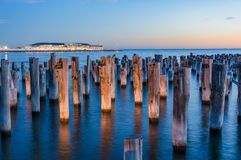 Old wooden pylons of historic Princes Pier in Port Melbourne. Illuminated old wooden pylons of historic Princes Pier in Port Melbourne at dusk. Australia. Long royalty free stock images