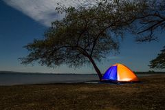 Illuminated orange camping tent under the tree Royalty Free Stock Photography