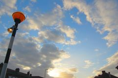 Illuminated orange safety crossing beacon set against peaceful evening light blue and fluffy white clouds royalty free stock photos
