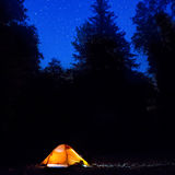 Illuminated orange tent at night in the forest Royalty Free Stock Images
