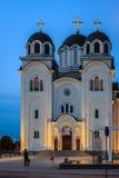 Valjevo, Kolubara, Serbia. The illuminated orthodox church of Valjevo, in the late evening light, with children playing on the church grounds Stock Image