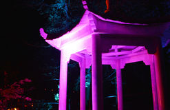 Purple Japanese Pagoda at Night. Multi-coloured spotlights illuminate a pagoda at night for a the Diwali Festival of Light at Robin Hill on the Isle of Wight Stock Photography