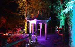 Illuminated Pagoda at Night. Multi-coloured spotlights illuminate a pagoda and wooden bridge for a the Diwali Festival of Light at Robin Hill on the Isle of Stock Photography