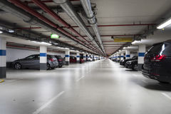 Illuminated parking garage. Some unrecognizable cars royalty free stock photo