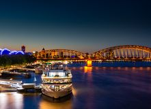 Illuminated passenger ships at the river Rhine in Cologne stock photography