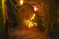 Illuminated Path Through The Woods. Lanterns lights an illuminated path through the woods at night during the Diwali Festival of Light at Robin Hill on the Isle Stock Photos