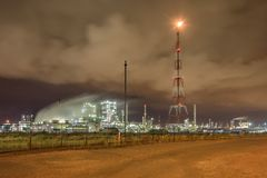 Massive petrochemical production plant against a cloudy sky at night, Port of Antwerp, Belgium. Illuminated petrochemical production plant against a cloudy blue royalty free stock photos