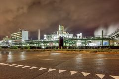 Massive petrochemical production plant against a cloudy sky at night, Port of Antwerp, Belgium. Illuminated petrochemical production plant against a cloudy blue royalty free stock images
