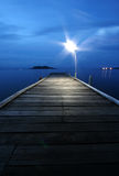 Illuminated Pier. A single light illuminating a pier by the sea Royalty Free Stock Photography