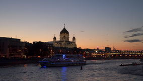 Illuminated pleasure boat. Sails across Moscow River against the background of the Cathedral of Christ the Savior at night stock video footage