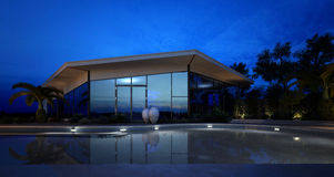 Illuminated pool in front of an upmarket villa Royalty Free Stock Photo