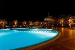Illuminated pool at night with tropical palms Royalty Free Stock Images