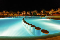 Illuminated pool at night with tropical palms Royalty Free Stock Photos