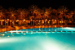 Illuminated pool at night with tropical palms Stock Photos