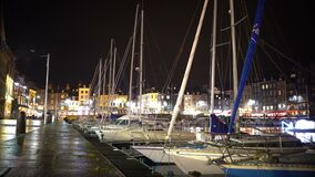 Illuminated port with parked yachts and boats, evening time in city, tourism stock video footage