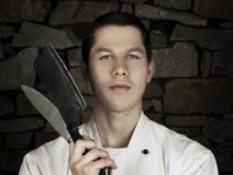Illuminated portrait of nice and attractive man chef in uniform on the stone wall background.  Man chef posing to camera with knif. E and cleaver chopper knife Royalty Free Stock Photos