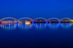Illuminated railway bridge at twilight. Riga, Latvia Stock Photos
