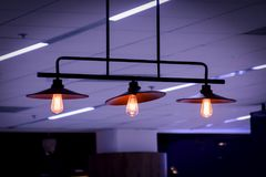 Illuminated retro style light bulbs. Decorative electric lamps hanging on the ceiling of dark room Royalty Free Stock Photo