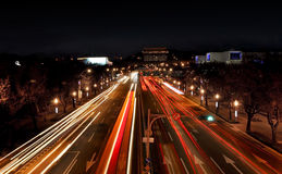 Illuminated road. Bright traffic lights on a freeway at night with a lot of fast cars Royalty Free Stock Image