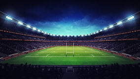 Illuminated rugby stadium with spectators and green grass Stock Image